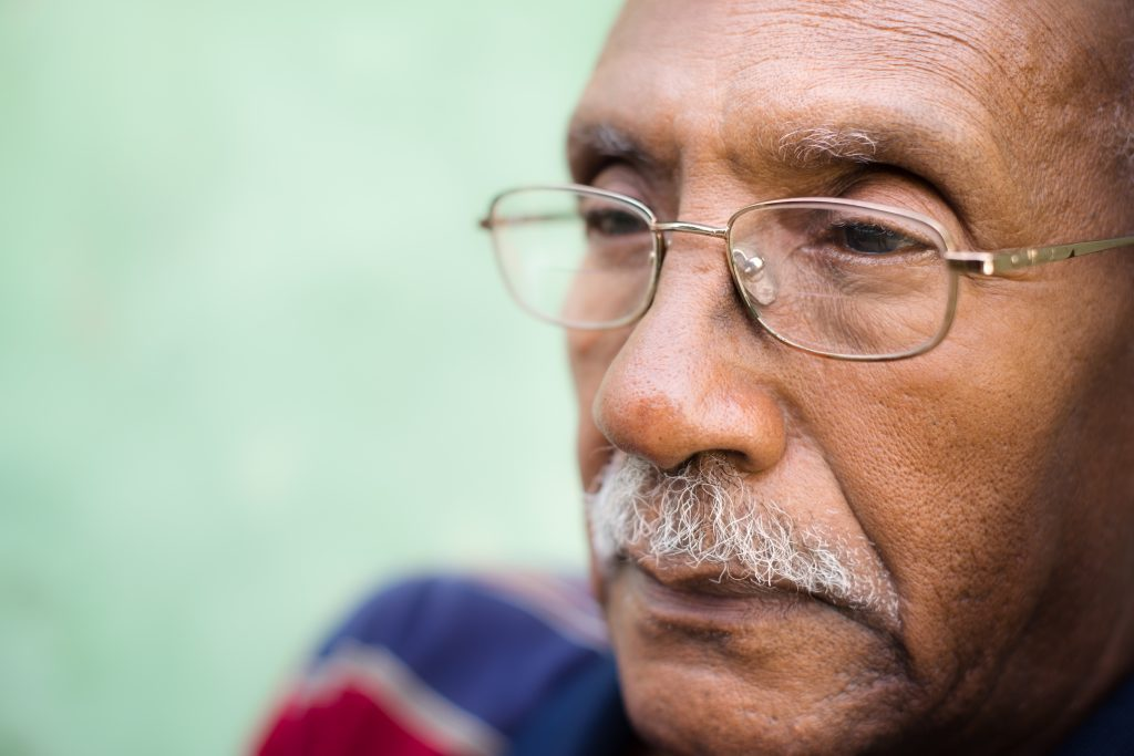 A close up image of a senior citizen man with glasses