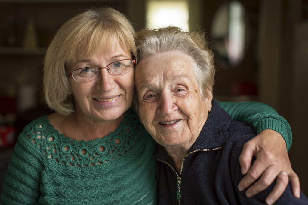 A middle aged and senior woman embracing and smiling.