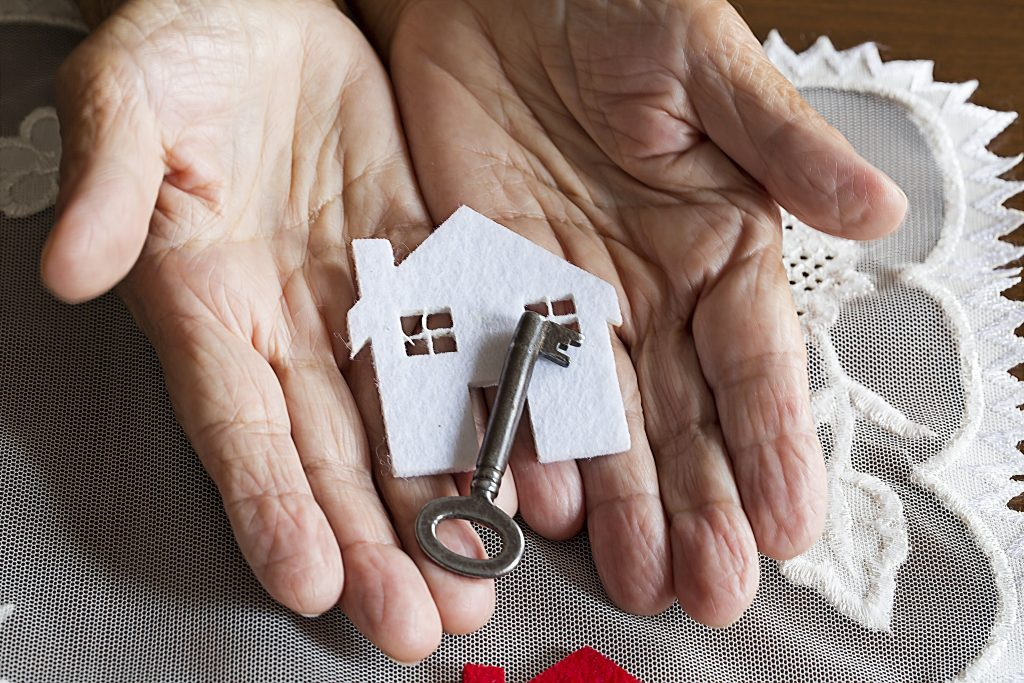 Senior person's hands holding paper cutout of a home with an old key on top
