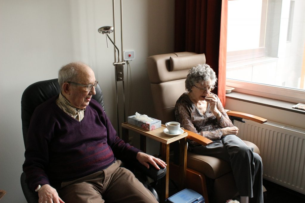 Senior couple sitting together in a nursing home having coffee.