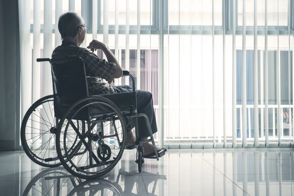 elderly man in wheelchair looking out the window